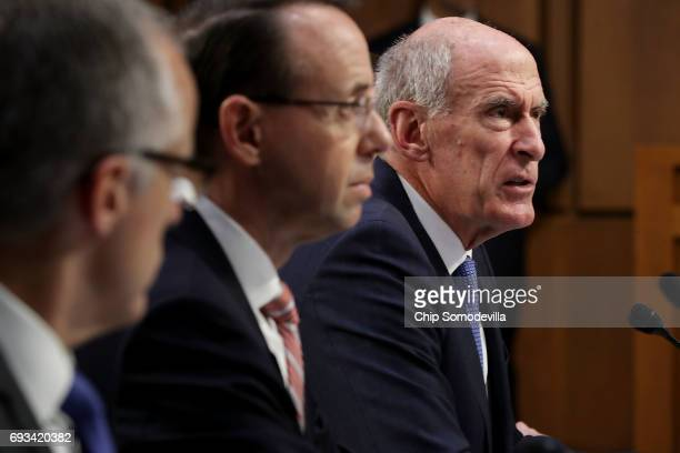 Acting FBI Director Andrew McCabe and Deputy Attorney General Rod Rosenstein listen as Director of National Intelligence Daniel Coats delivers...
