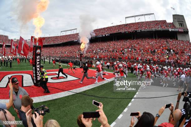 Acting Head Coach Ryan Day of the Ohio State Buckeyes leads the team on to the field to play against the Oregon State Beavers at Ohio Stadium on...