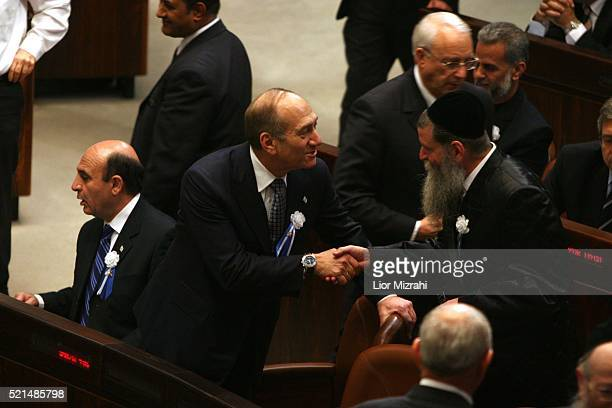 Acting Israeli Prime Minister Ehud Olmert shakes hands with a new parliament member at an inaugural session of the new parliament in Jerusalem Monday...