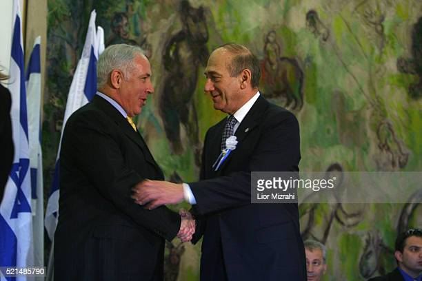 Acting Israeli Prime Minister Ehud Olmert shakes hands with Likud party leader Benjamin Netanyahu after an inaugural session of the new parliament in...