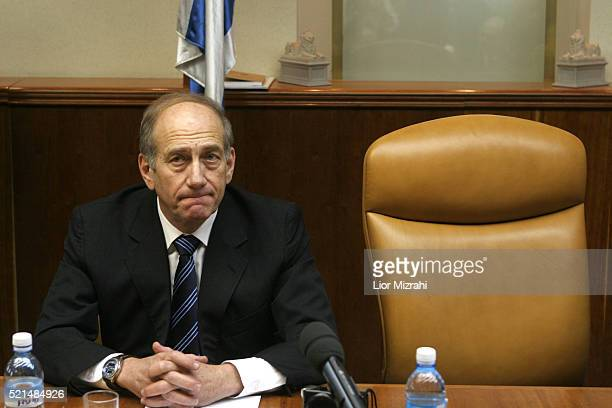 Acting Israeli Prime Minister Ehud Olmert sits next to the empty chair of Ariel Sharon at a special government meeting, at the Prime Minister's...