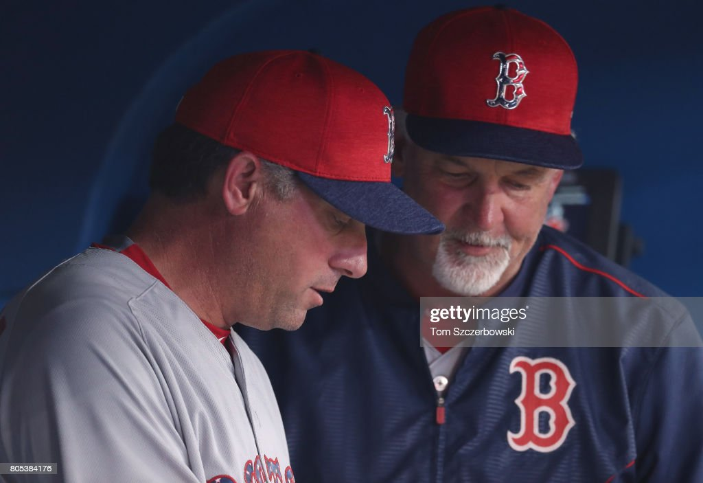 Acting manager Gary Disarcina #10 of the Boston Red Sox talks to pitching coach Carl Willis #54 in the dugout during the absence of manager John Farrell #53 during MLB game action against the Toronto Blue Jays at Rogers Centre on July 1, 2017 in Toronto, Canada.