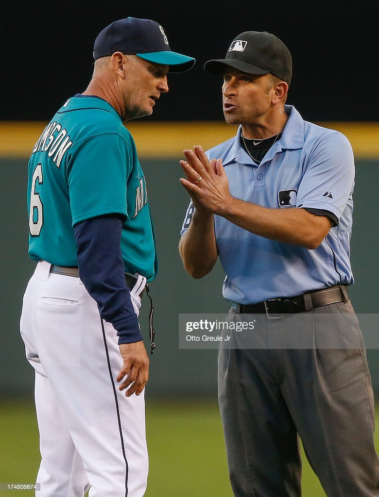 Acting manager Robby Thompson #6 of the Seattle Mariners listens to second base umpire Chris Guccione #68 explain a force out call of Dustin Ackley (not pictured) in the fifth inning against the Minnesota Twins at Safeco Field on July 26, 2013 in Seattle, Washington.