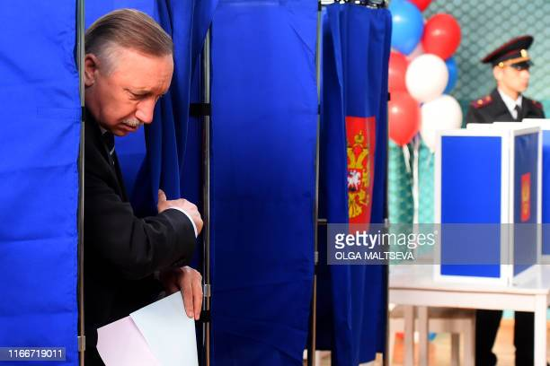 Acting SaintPetersburg Governor Alexander Beglov gets out of a polling booth prior to casting his vote at a polling station during the governor's...