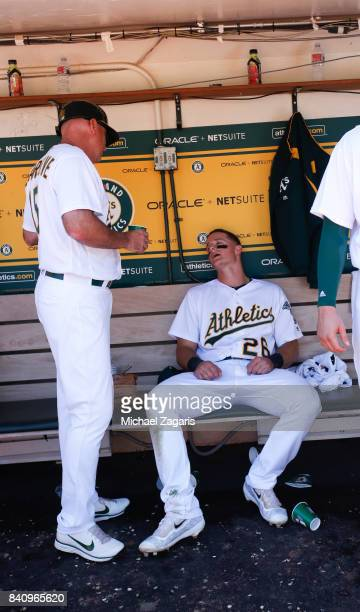 Acting Third Base Coach Steve Scarsone and Matt Chapman of the Oakland Athletics talk in the dugout during the game against the Minnesota Twins at...