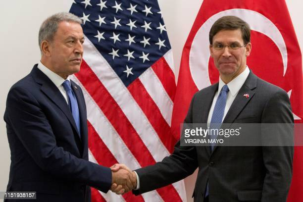 Acting US Secretary for Defense Mark Esper shakes hands with Turkish Defense Minister Hulusi Akar prior to a meeting with NATO's defense ministers at...