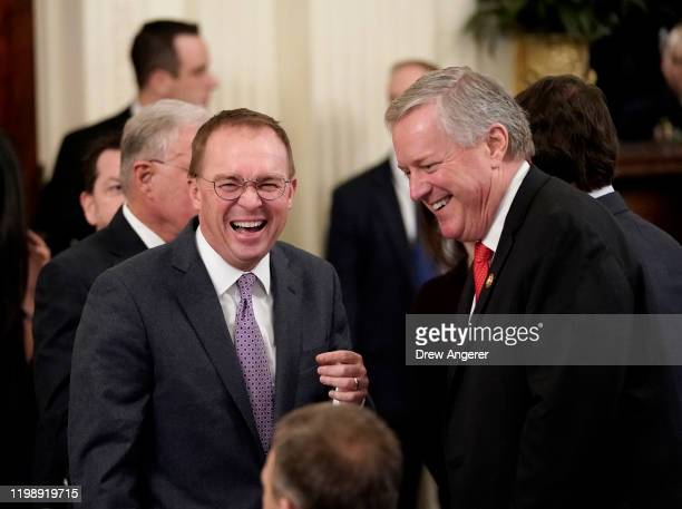Acting White House Chief of Staff Mick Mulvaney and Rep Mark Meadows talk before US President Donald Trump speaks to the media in the East Room of...