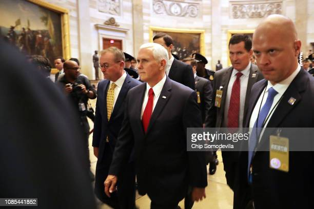 Acting White House Chief of Staff Mick Mulvaney and Vice President Mike Pence walk from the House of Representatives to the Senate while negotiating...