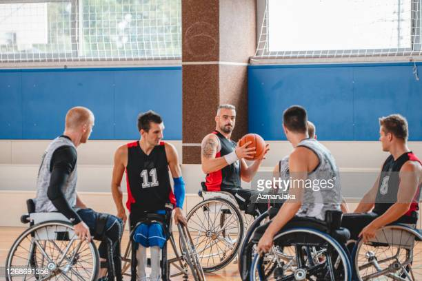 action between male wheelchair basketball players - competition group stock pictures, royalty-free photos & images