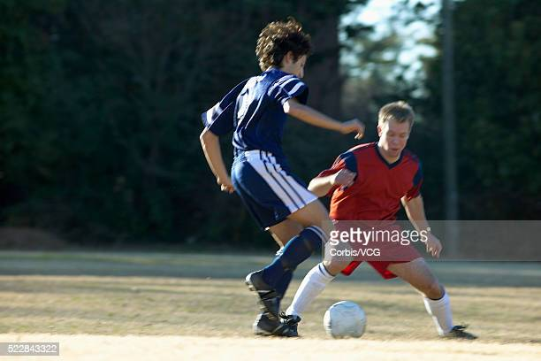 action during soccer game - tacler photos et images de collection