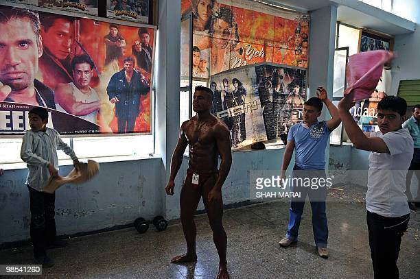 Action film posters cover a preparation area as an Afghan bodybuilder's assistants fan him before he goes on stage to compete at a cinema in Kabul on...