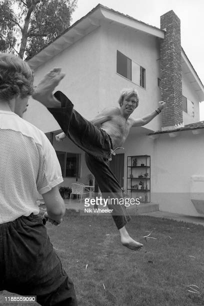 Action hero movie star Chuck Norris practices kung fu style moves with a trainer in back yard of his house in Palos Verdes circa 1978
