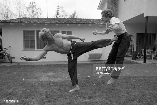 LOS ANGELES JANUARY 1978 Action hero movie star Chuck Norris practices kung fu style moves with his trainer on the lawn of his back yard of his home...