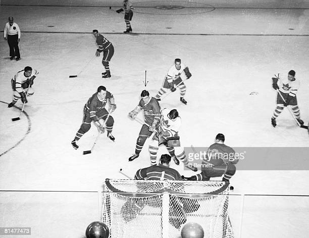 Action in front of the bet during an ice hockey game between the Montreal Canadiens and the Toronto Maple Leafs, 1940s. Among those pictured are...