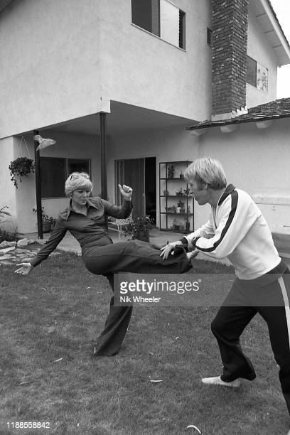 LOS ANGELES JANUARY 1978 Action movie actor Chuck Norris practices some of his Chun Kuk Do moves with his wife Dianne on lawn in the garden of their...