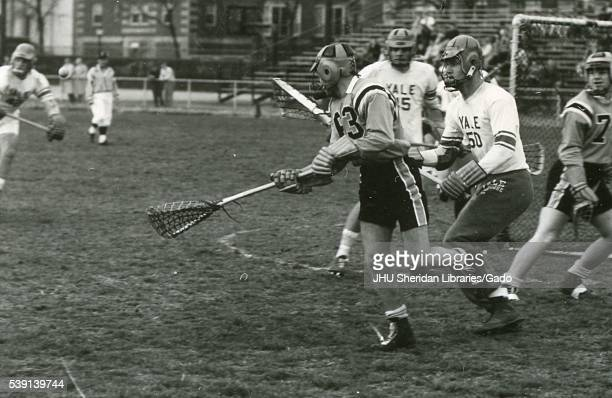Action photograph of male Johns Hopkins University lacrosse player on the field surrounded by multiple Yale University player during a game 1964