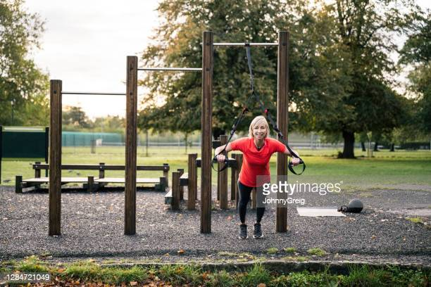 action portrait of athlete doing suspension training at park - clapham common stock pictures, royalty-free photos & images