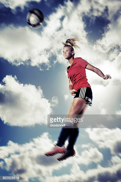 Action Portrait of Ball Headed by Female Teenage Soccer Player