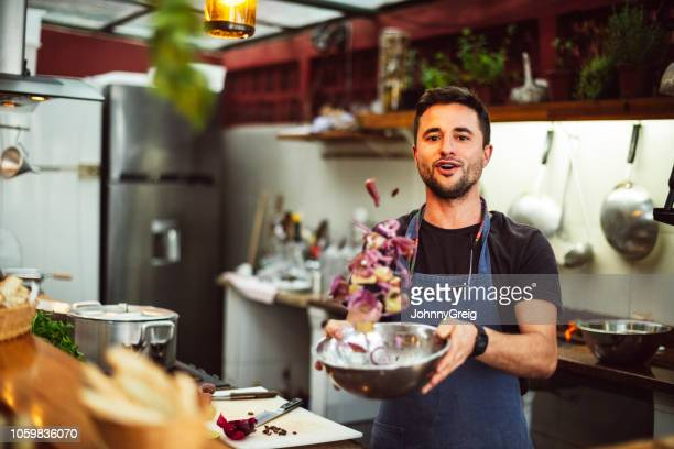 action portrait of male chef tossing ingredients in bowl - lanciare foto e immagini stock