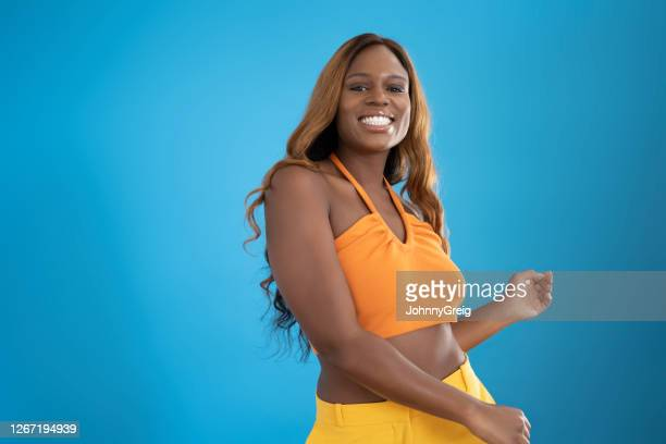 action portrait of mid 20s longhaired black woman dancing - halter neck stock pictures, royalty-free photos & images