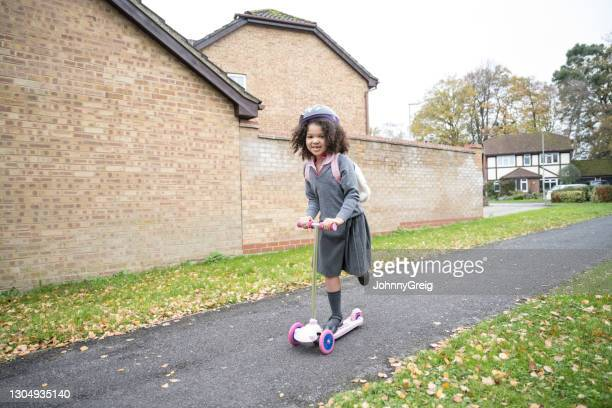 action portrait of mixed race girl riding scooter to school - mid length hair stock pictures, royalty-free photos & images