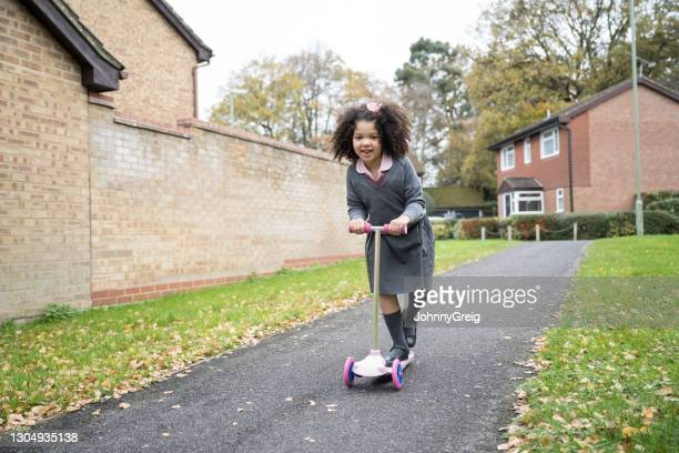 action portrait of mixed race schoolgirl riding push scooter - mid length hair stock pictures, royalty-free photos & images