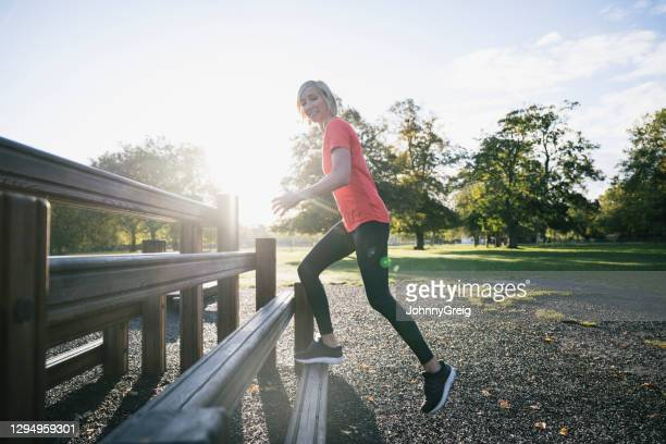 action portrait of sportswoman doing step-ups at public park - clapham common stock pictures, royalty-free photos & images