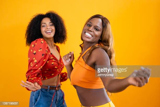 action portrait of young black women dancing together - halter neck stock pictures, royalty-free photos & images