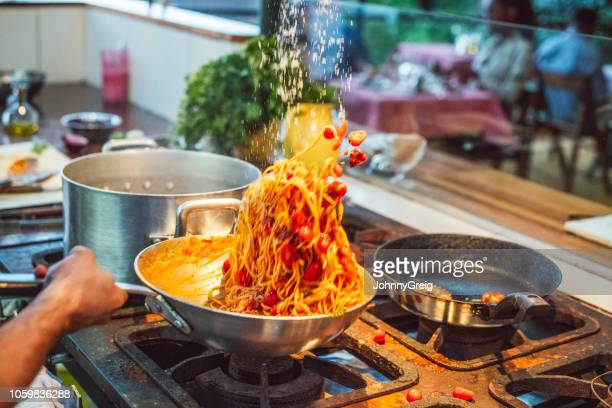 action shot of chef tossing fresh pasta in wok on gas hob - throwing stock pictures, royalty-free photos & images