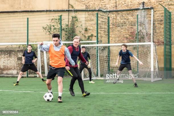 action shot of five football players playing on an outdoor pitch - amateur stock pictures, royalty-free photos & images