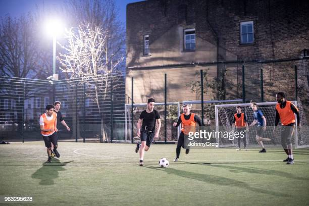 Action shot of footballers on an urban pitch at night with two players running for the ball