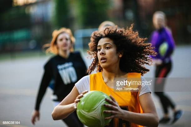 action shot of netball player catching ball on outdoor sports court - extra long stock pictures, royalty-free photos & images