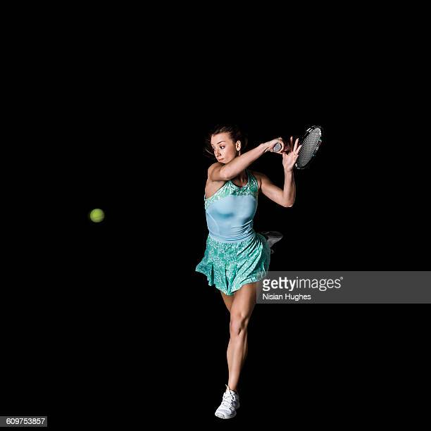 Action shot of woman playing tennis, forhand