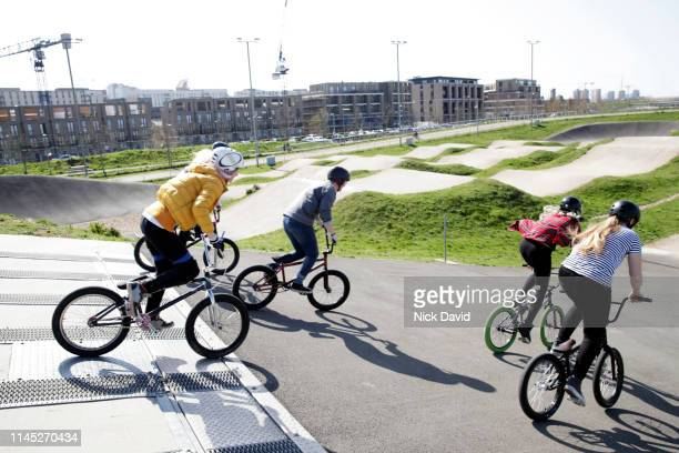 action shot of women on bmxs cycling downhill - bmx track london stock pictures, royalty-free photos & images