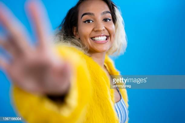 action studio portrait of young mixed race woman dancing - reaching stock pictures, royalty-free photos & images