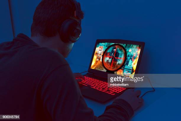 action video game plays out on gaming laptop at night - esports stock pictures, royalty-free photos & images