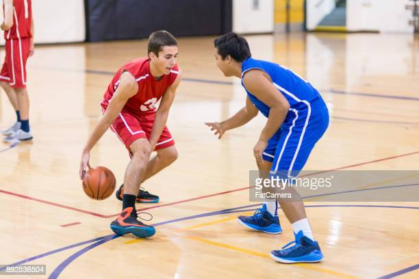 action-packed boy's high school basketball game - basketball shoe stock photos and pictures