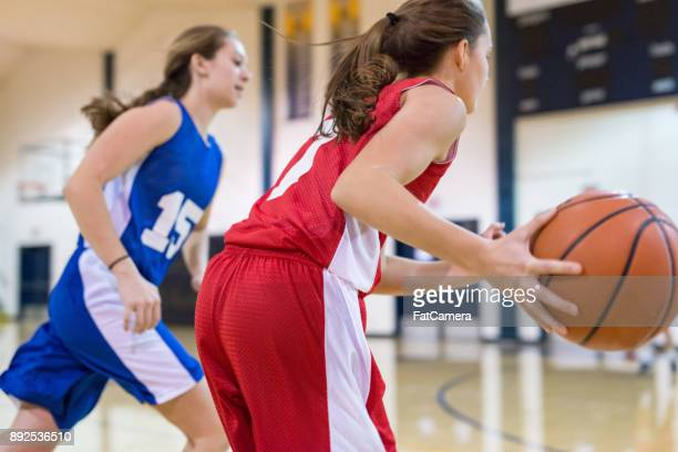 action-packed girl's high school basketball game - basketball shoe stock photos and pictures