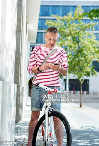 active and fit senior man in his 60s with his stylish single speed city bike uses phone. - ems forster productions stock pictures, royalty-free photos & images