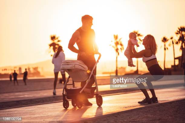 active and sportive family by the beach with their baby - three wheeled pushchair stock pictures, royalty-free photos & images