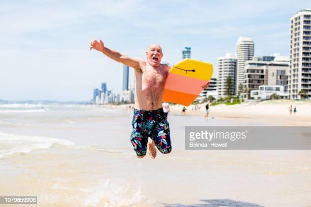 active australian senior enjoying a day on gold coast beach - gold coast stockfoto's en -beelden
