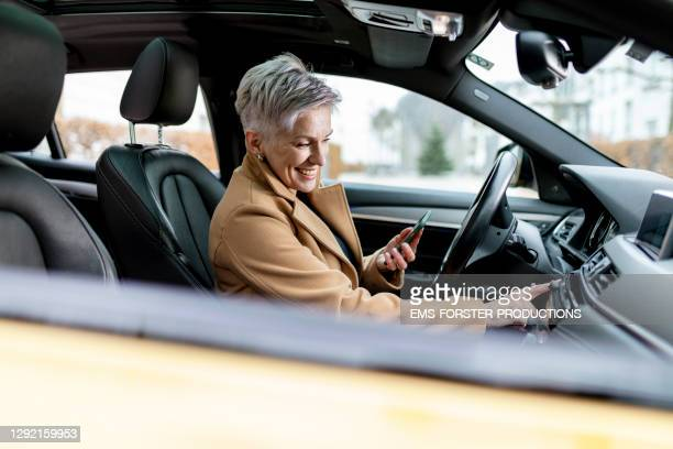 active bestager women is using smart phone to start a sharing car - ブルートゥース ストックフォトと画像
