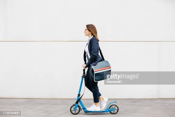 active businesswoman riding scooter in the city - crossbody bag stock pictures, royalty-free photos & images