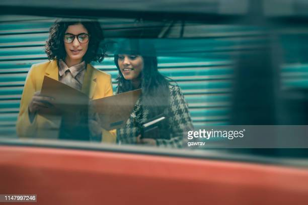 active businesswomen discuss project by the side of busy road. - differential focus stock pictures, royalty-free photos & images