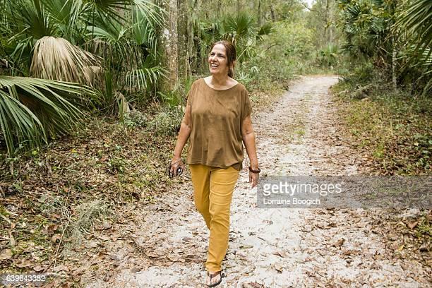 active central florida hispanic senior woman walking nature trail orlando - florida nature stock pictures, royalty-free photos & images