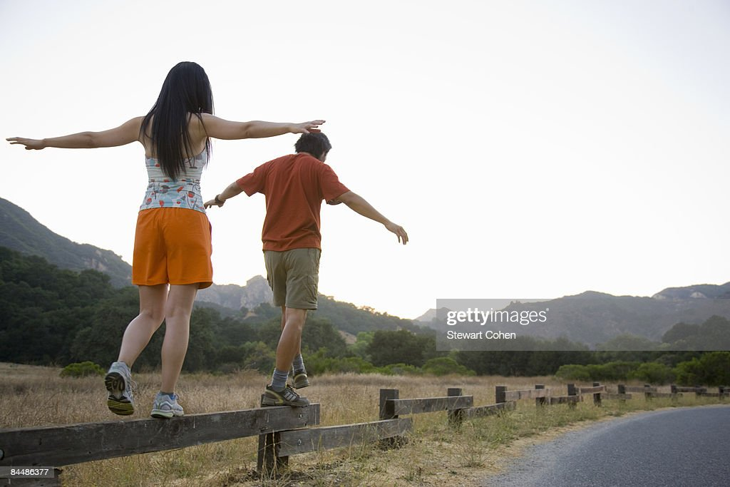 Active couple balancing on low fence. : Stock Photo
