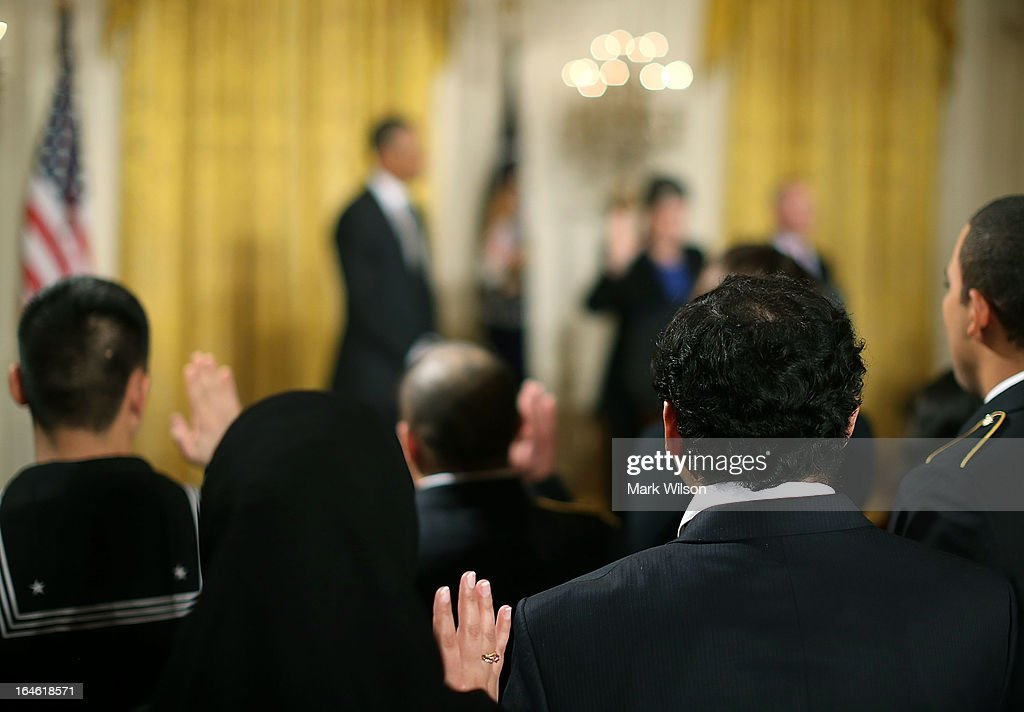 Active duty service members hold up their hands while U.S. President Barack Obama listens to Homeland Security Secretary Janet Napolitano administer the oath of allegiance during a naturalization ceremony in the East Room of the White House on March 25, 2013 in Washington DC. Napolitano administered the oath of allegiance to active duty service members and civilians officially granting them United States citizenship.