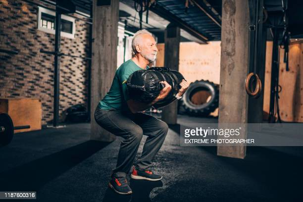 active elderly man doing a squat exercise with a core bag with the guidance of a personal fitness trainer in a gym area of a gym - sandbag stock pictures, royalty-free photos & images