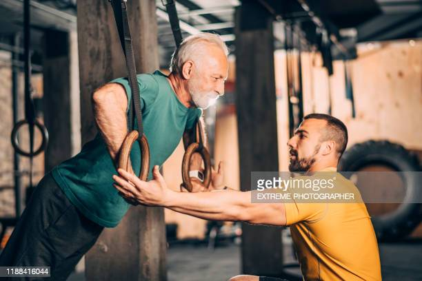 active elderly sportsman doing an exercise on gymnastics rings with the help of his personal fitness trainer in a gym gym arena - gymnastics stock pictures, royalty-free photos & images