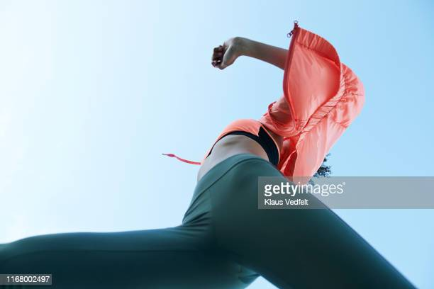 active female athlete against clear sky - fast fashion stock pictures, royalty-free photos & images